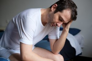fatigued man sitting in bed is thinking about how Malegenix can be helpful