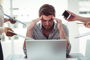 man stressed at work trying to read about Malegenix online