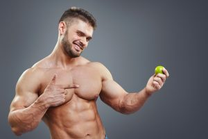 ripped shirtless guy who uses Malegenix holding a lime rich in vitamin C