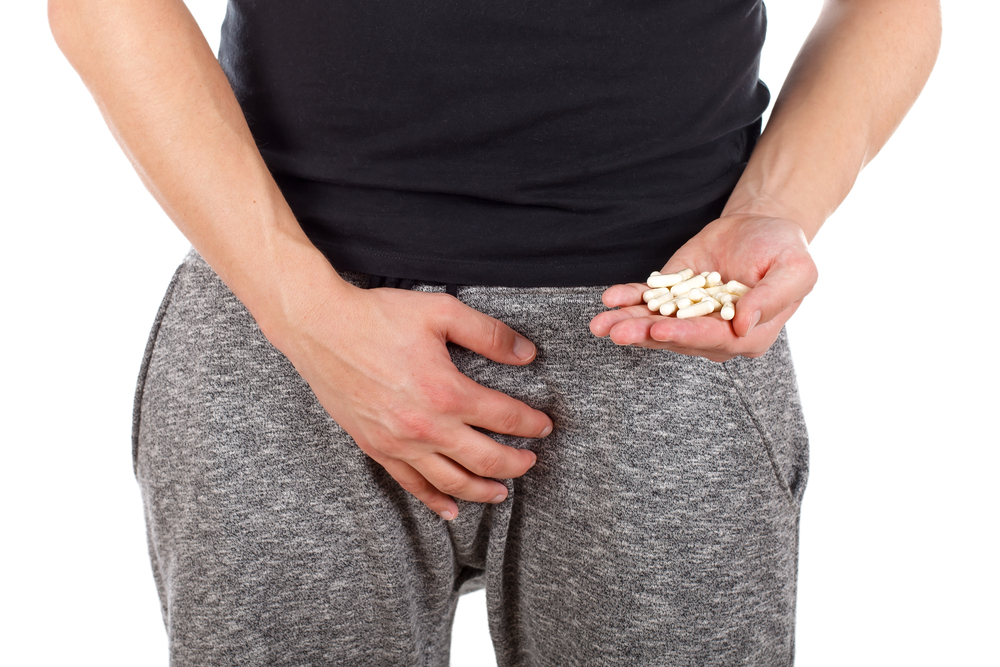 man holding Malegenix pills while clutching his junk with the other hand
