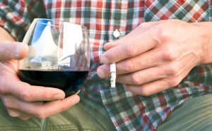 man holding wine and cigarette can address erectile dysfunction with Malegenix supplement
