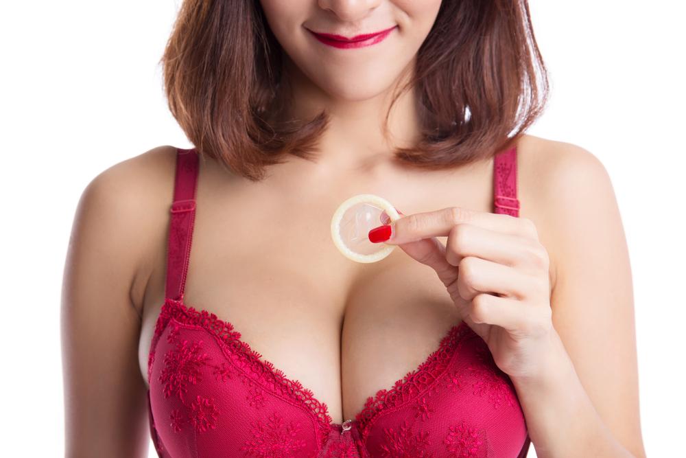 woman in red bra holding condom for partner using Malegenix