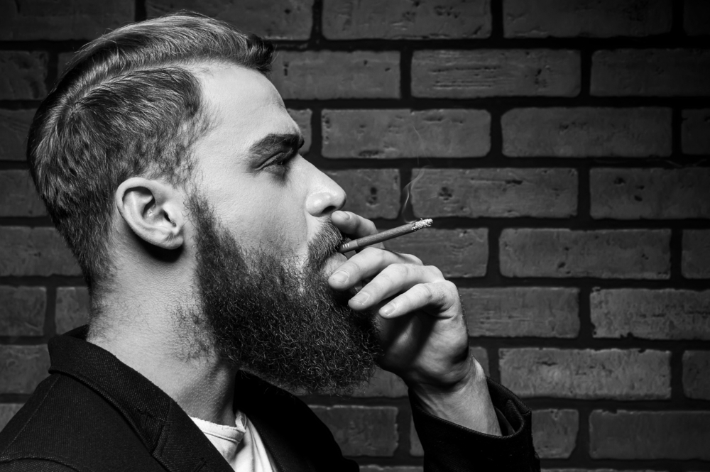 man thinking to quit smoking and give Malegenix male enhancement supplement a try