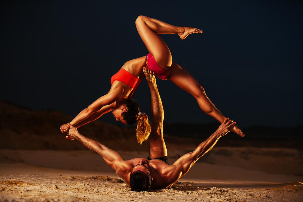 couple's yoga on the beach after man takes Malegenix male enhancement supplement