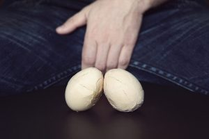 broken eggs against man's crotch signifying testicular damage can benefit from Malegenix male enhancement supplement