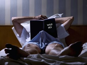 man reading about wild sex while having an erection due to Malegenix male enhancement supplement
