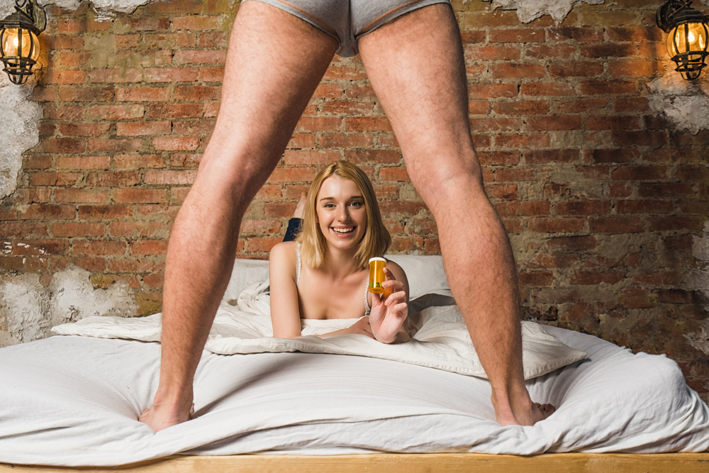 man standing on bed over woman holding a bottle of Malegenix male enhancement supplement